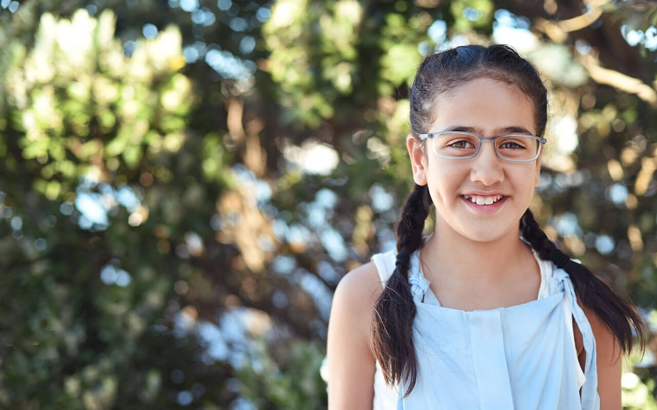 Girl smiling while wearing her new glasses